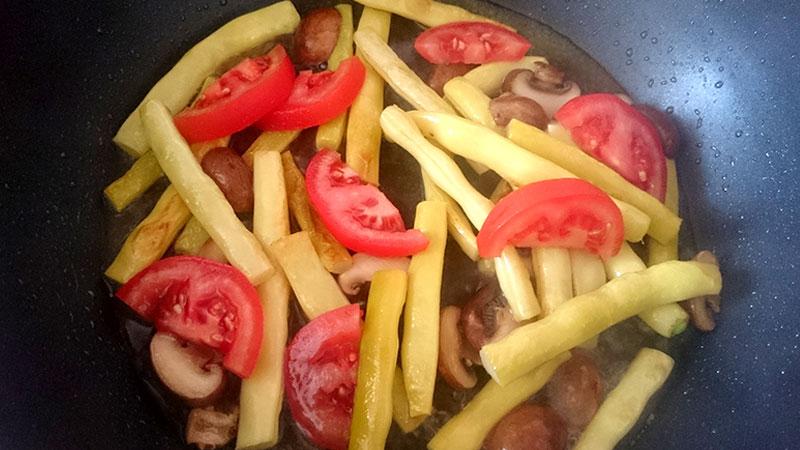 Die Stangenbohne werden mit den Champignons gut angebraten, bevor die Tomaten mit dem Weißwein dazu gegeben werden.